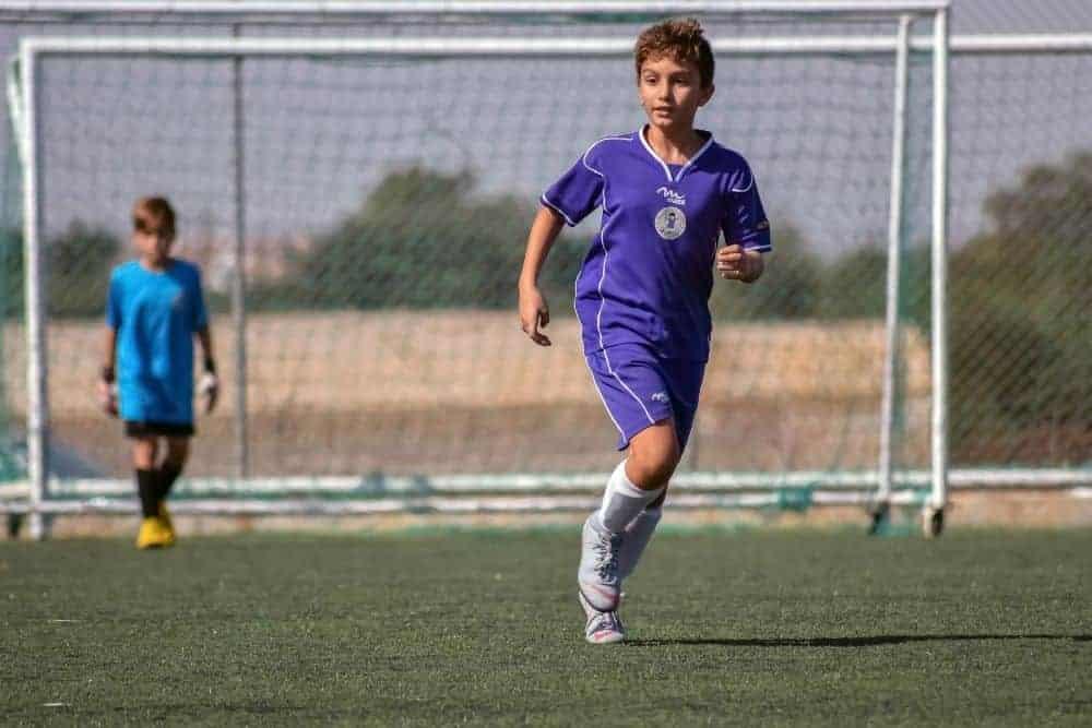 Cậu bé áo tím đang chạy trên sân bóng