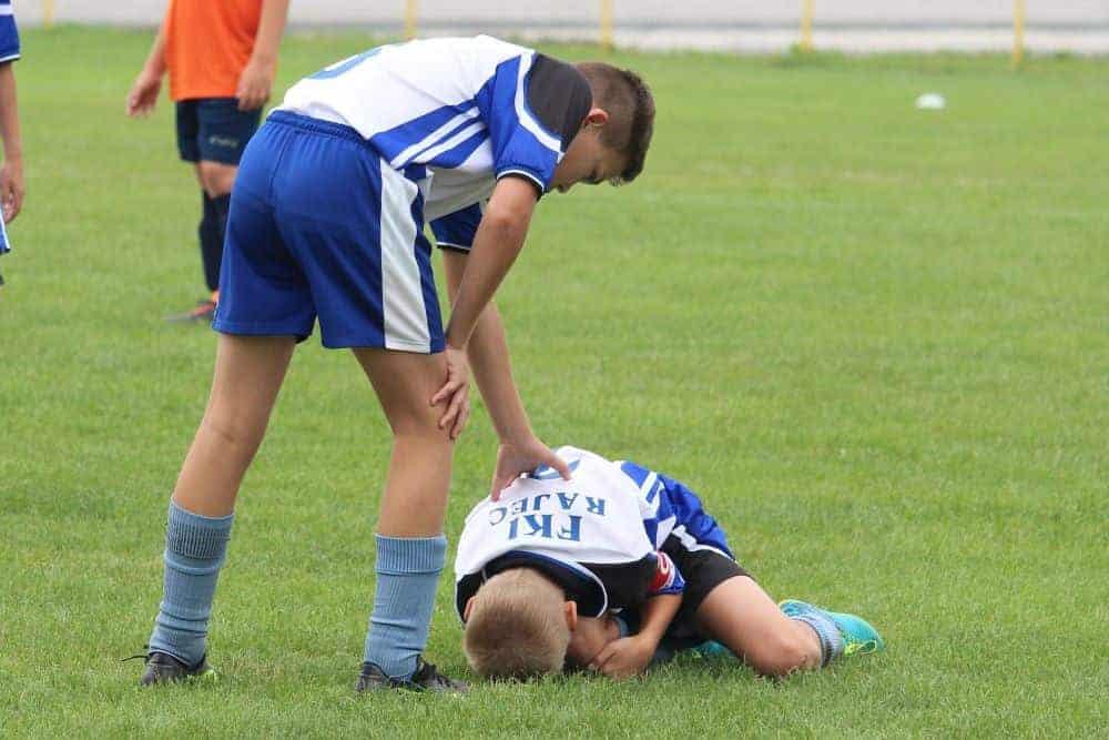 Một cầu thủ đnag ôm chân đau đớn, người đồng đội đang hỏi han