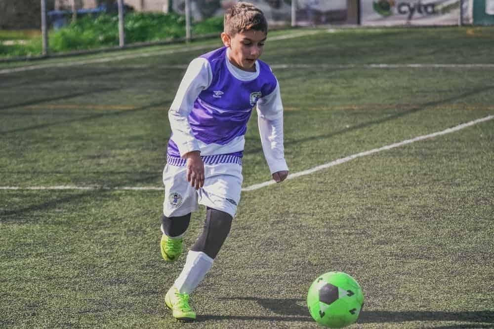 Một cậu bé mặc đồ đá bóng màu tím đang dẫn bóng màu xanh