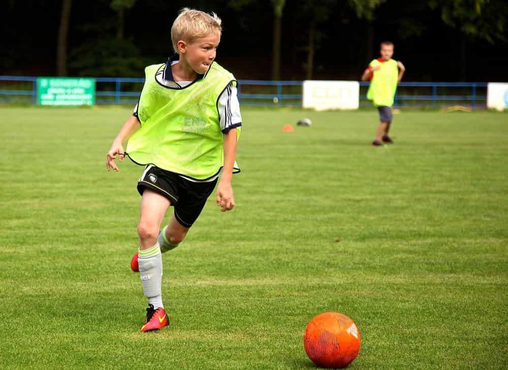 Một câu bé mặc áo dự bị đang dốc quả bóng