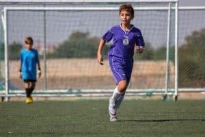 Một cậu bé mặc quần áo đá bóng màu tím dang chạy trên sân cỏ
