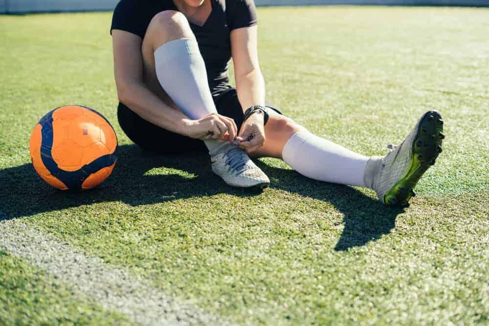 Một người đang ngồi cạnh quả bóng và cột dây giày
