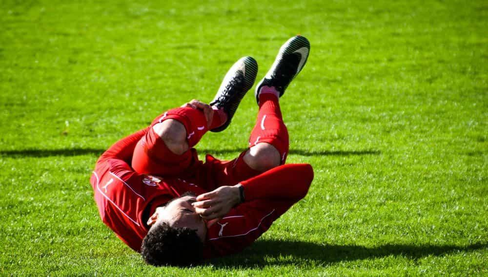 Một cầu thủ nằm ôm chân trái do bị chấn thương