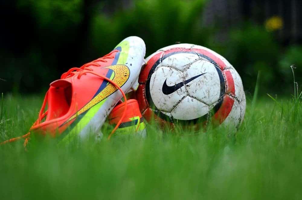 Một quả bóng đang nằm cạnh một đôi giày nike cam trắng