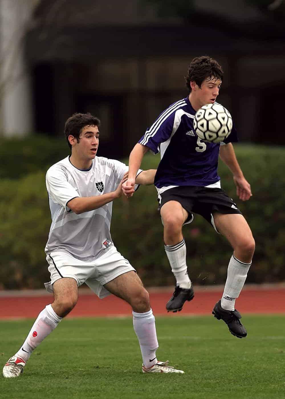 2 cầu thủ đang tranh chấp bóng, cầu thủ áo đen đang nhảy lên hứng bóng còn cầu thủ áo trắng đang đứng trụ
