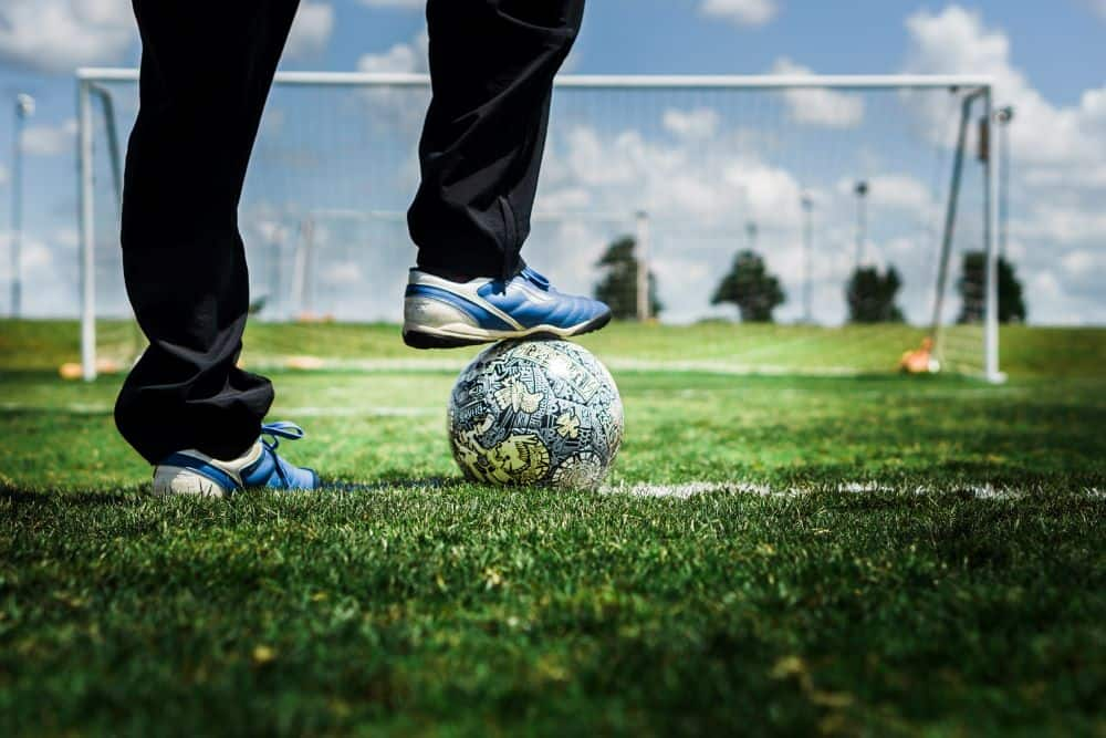 Một người mặc quần dài, đeo giày bóng đá mày xanh nước biển hãm trái bóng bằng lòng bàn chân