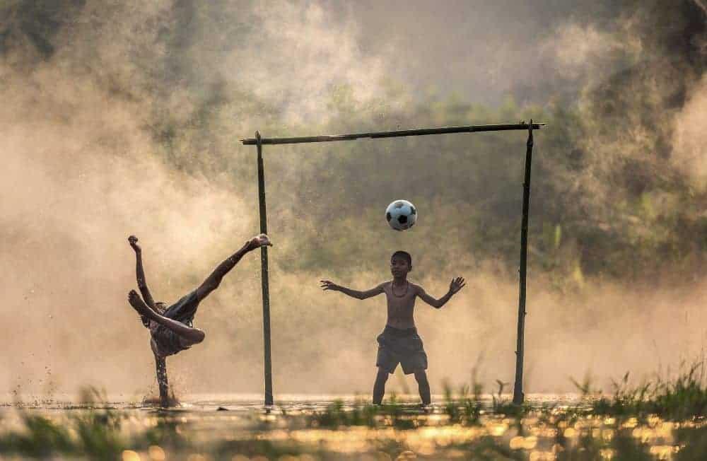 một cậu bé đang vô lê quả bóng và một cậu bé đang cuẩn bị chụp bóng