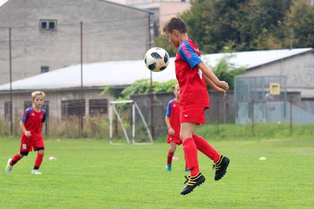Một cậu bé đang đỡ bóng bằng ngực, cậu bé mặc áo đỏ và đang nhảy lên để khống chế bóng