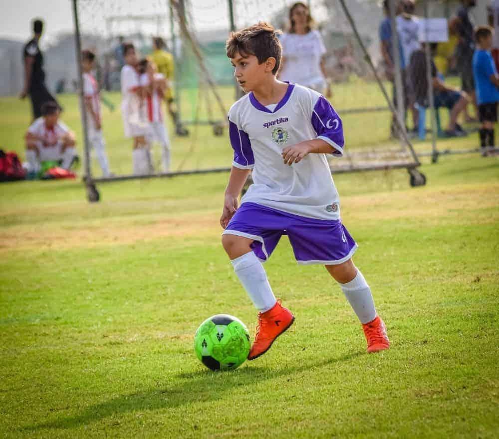 Một cậu bé mặc áo trắng tím đang dẫn quả bóng màu xanh trên sân cỏ