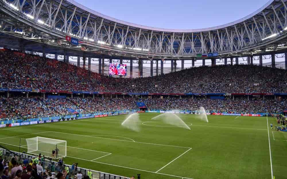 Sân vận động đang được tưới nước trước trận đấu, chật kín khán giả