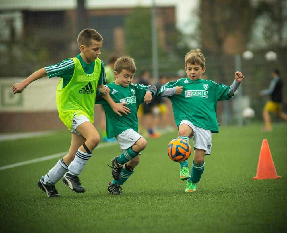 3 cậu bé đang tranh chấp bóng, trong đó có 1 cậu bé cao hơn 2 cậu bé còn lại và mặc áo tập, cả ba đều mặc áo đá bóng màu xanh