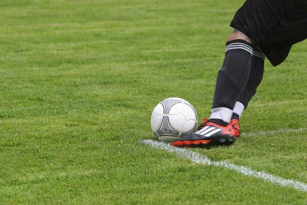 Một cầu thủ băng cổ chân đang sút bóng