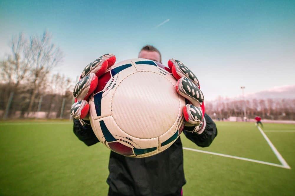 Một thủ môn đang ôm quả bóng chĩa về óng kính