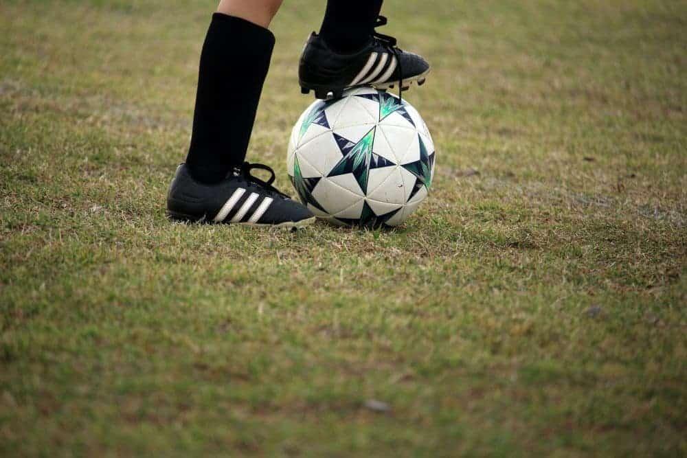 Một cầu thủ nhí đang dùng gần giầy giữ bóng