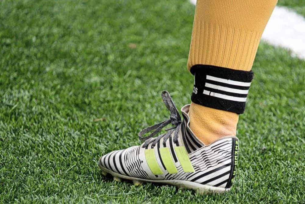 Chân cầu thủ bóng đá mang tất vàng và giày xám
