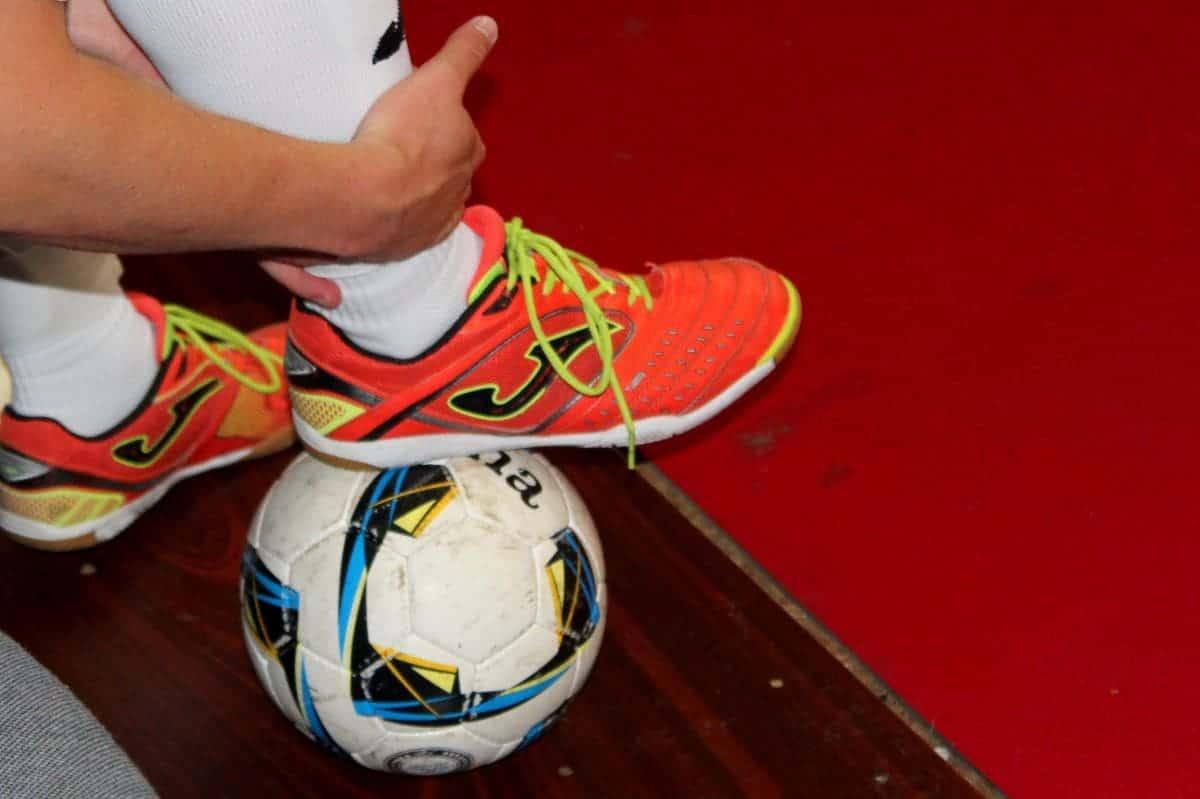 Một người đeo giày đang dậm lên quả bóng