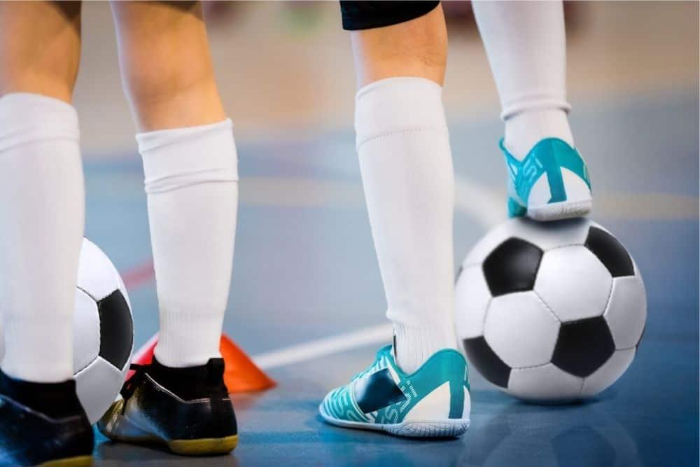 Một cầu thủ futsal đang dùng gầm giày hãm bóng và đứng bên cạnh là cầu thủ futsal khác