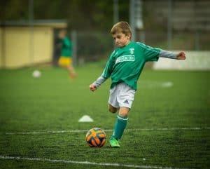 Một cầu thủ nhí mặc áo xanh lá sút bóng