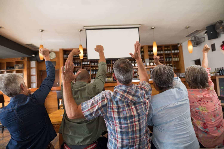 Một nhóm người đang cổ vũ bóng đá trước màn hình máy chiếu