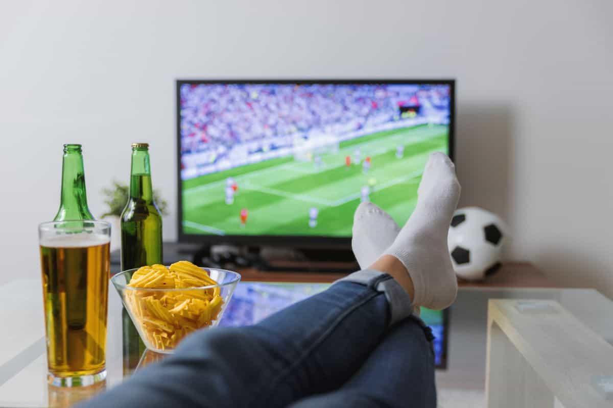 Một người đang bắt chéo chân xem bóng đá, ăn bắp ngô và uống bia