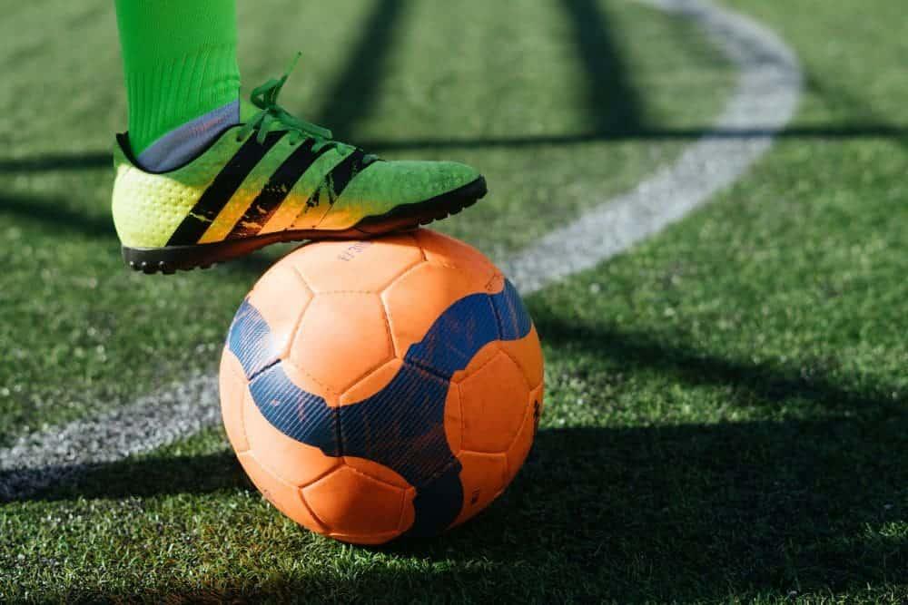 Một cầu thủ đang dùng giày sân cỏ nhân tạo hãm bóng