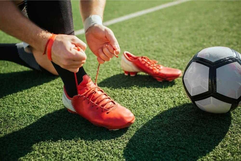 Một cầu thủ đang cột dây giày