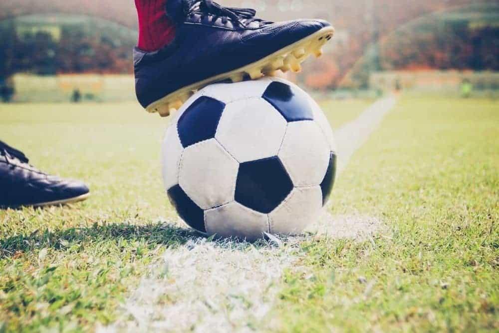 Một cầu thủ đi giày đen hãm bóng bằng gầm giày