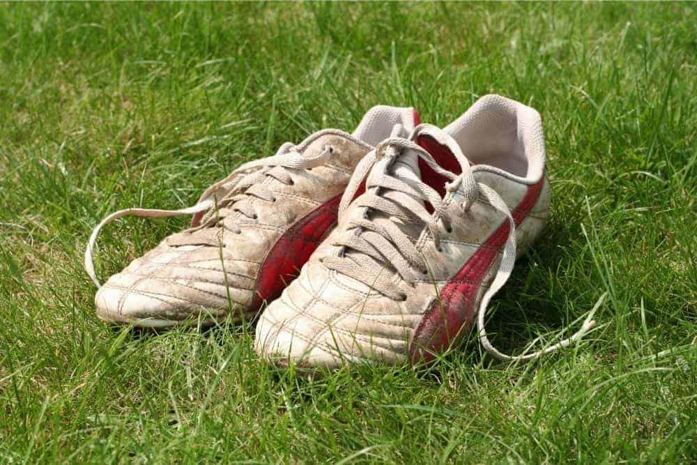Một đôi giày bóng đá khá bẩn nằm trên bề mặt cỏ