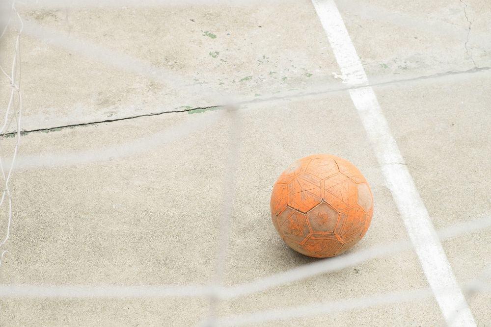 Quả bóng đá màu cam nằm sát đường biên