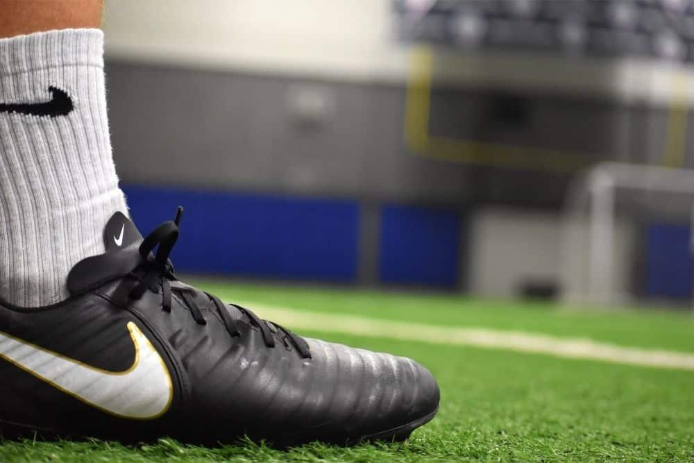 Một người đeo giày đá bóng đang đứng trên cỏ nhân tạo