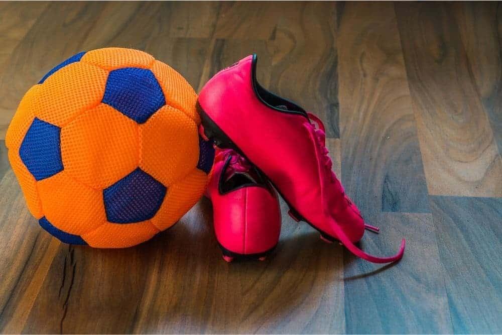 Đôi giày đỏ và quả bóng đá cam