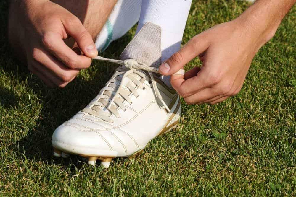 Một người đang thắt dây giày đá bóng