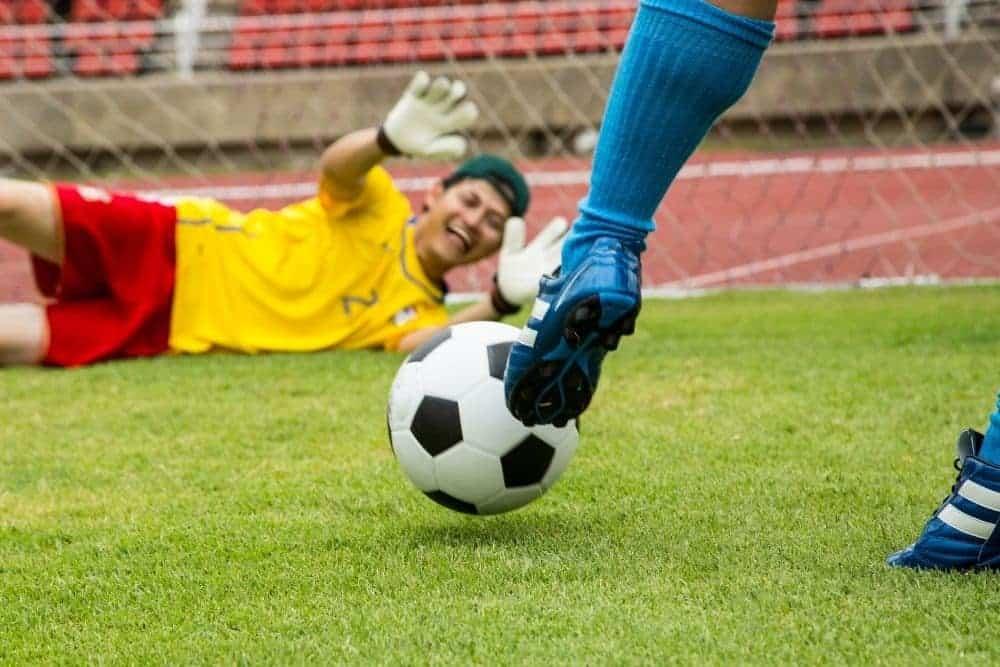 Cầu thủ áo xanh đang chuẩn bị sút bóng