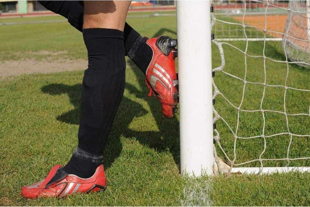 Một cầu thủ đeo giày bóng đá đỏ không dây đang tựa vào cột dọc cầu môn