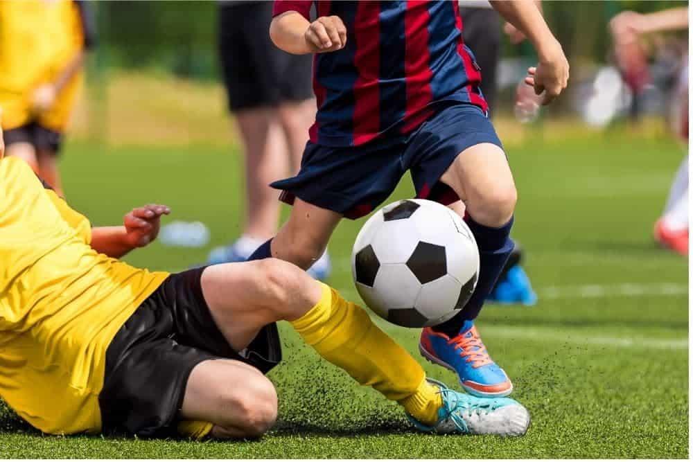 1 cầu thủ áo vàng tắc bóng của cầu thủ áo sọc đỏ xanh